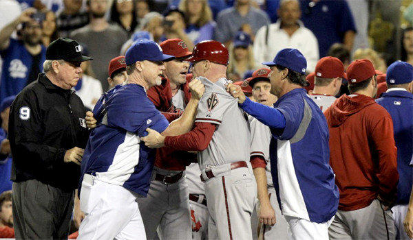 Diamondbacks third base coach Matt Williams, center, is grabbed by Dodgers hitting coach Mark McGwire, left, and L.A. Manager Don Mattingly, right, during a bench clearing brawl on Tuesday.