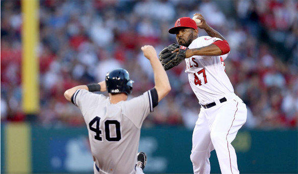 Howie Kendrick gets the force out on Reid Brignac at second before throwing to first to complete the double play in the fourth inning of the Angels' 5-2 victory over the New York Yankees on Friday.