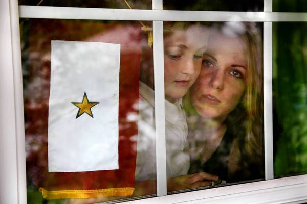 Megan Griffin holds her son Corey, 6, next to the gold star that she hangs in her window in honor of her husband, Michael Griffin, who committed suicide in 2009, eight months after enlisting in the Army.