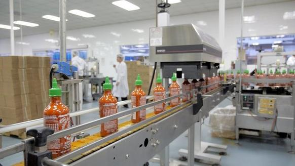 Bottles on a conveyor belt at the Huy Fong Foods facility in Rosemead are shown.