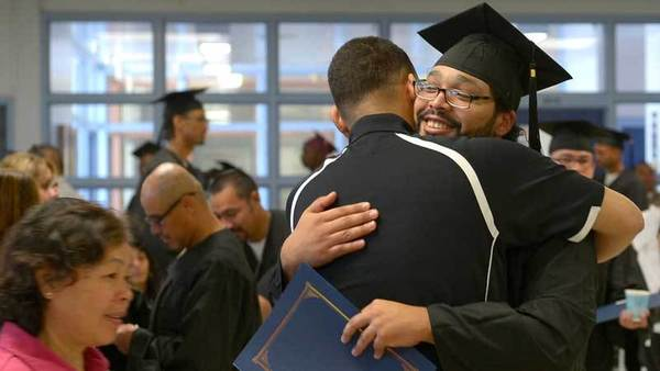 An inmate of Calipatria State Prison embraces his family member after a graduation ceremony held for the 48 inmates that completed requirements to earn a GED on Friday morning at the prison.