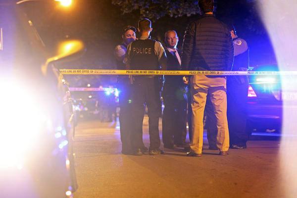 Authorities investigate the scene of a double shooting in the Austin neighborhood early Saturday morning.