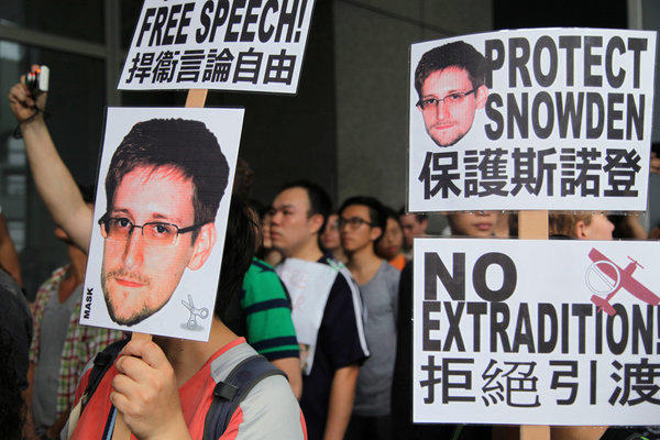 Protesters hold placards outside government headquarters during a rally in Hong Kong on Saturday in support of Edward Snowden, the former National Security Agency contractor.