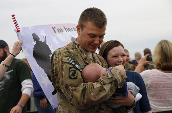 Returning Illinois National Guard member Robert Boone, of Oak Lawn, holds his 7-month-old son Robert Jr. for the first time shortly after returning from Afghanistan in Chicago on Saturday