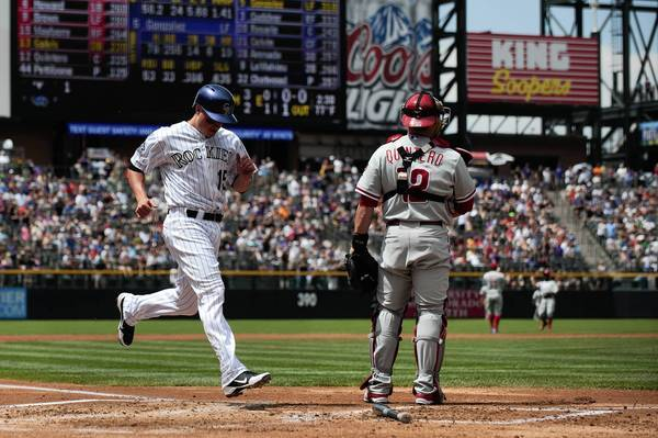Jordan Pacheco #15 of the Colorado Rockies scores on a double by Carlos Gonzalez #5 (not pictured) as Humberto Quintero #12 of the Philadelphia Phillies awaits a throw in the first inning of a game at Coors Field on June 15, 2013 in Denver, Colorado.