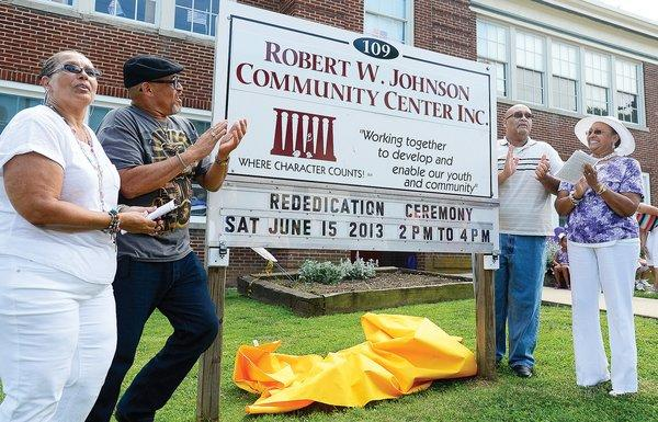 The late Robert W. Johnson's children, from left, Pam (Johnson) Sonttag, Stephen L. Johnson Sr, and Roderick Johnson, along with their mother Tish Johnson, right, unveiled the new Robert W. Johnson Community Center Inc. sign Saturday at 109 W. North Ave. in Hagerstown.