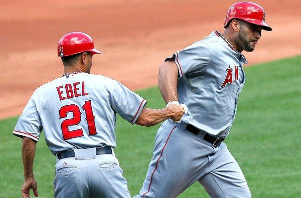 Angels first baseman Albert Pujols is congratulated by third base coach Dino Ebel after hitting a home run against the Boston Red Sox last weekend.