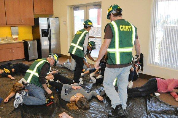 Volunteers for the city's CERT program assess a room of victims during a START exercise.