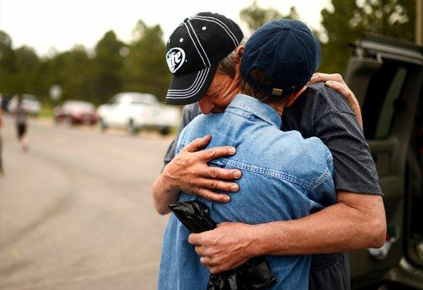 Black Forest fire evacuee Cindy Miller, left, hugs her husband, Ray, before he checks on their property with an El Paso County sheriff's escort in Colorado Springs, Colo. The Millers lost their house in the fire.
