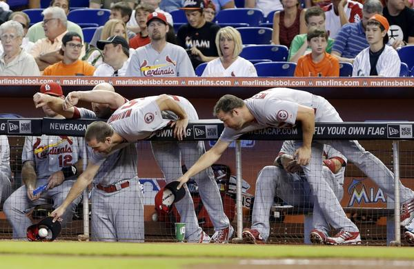 St. Louis pitcher Adam Wainwright snags a foul ball, beating out fellow pitcher Jake Westbrook during the first inning of the Cardinals' game against the Miami Marlins on Saturday.