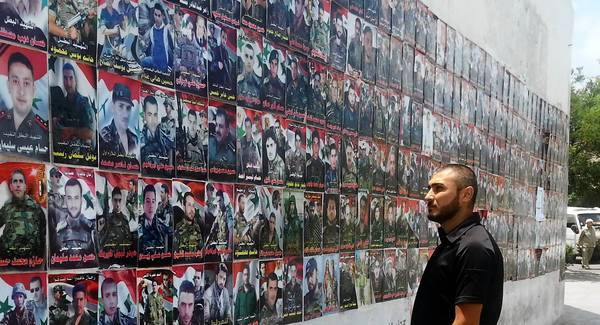 "Samer Ahmed scans the colorful posters of ""martyrs wall,"" the sons of Tartus who have been killed fighting for the government of Syrian President Bashar Assad."