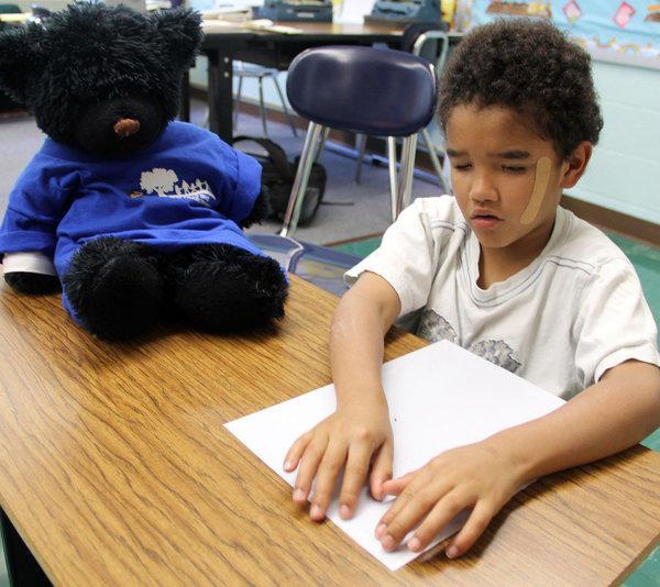 Trashawn Howard, 7, works in the Braille room with Sir Black Bear-y.