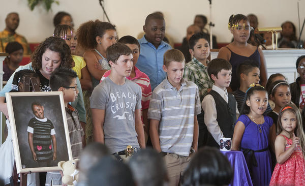 Students who attended South Bend's Veritas Academy with 6-year-old Shirley Mundia during the recently completed school year sing a song in her honor Saturday at a memorial service for Shirley at the Pentecostal Cathedral Church of God in Christ in South Bend. Three days after her graduation from kindergarten, Shirley was stabbed to death by her father, Edward Mwaura, who in turn was shot to death by police. At left is a teddy bear and portrait of Shirley.