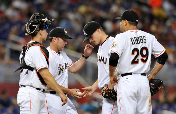 Jun 15, 2013; Miami, FL, USA; Miami Marlins manager Mike Redmond (second from left) takes starting pitcher Tom Koehler (center) out of the game during the fifth inning as first baseman Greg Dobbs (far right) and catcher Rob Brantly (left) look in against the St. Louis Cardinals at Marlins Park. Mandatory Credit: Steve Mitchell-USA TODAY Sports ORG XMIT: USATSI-122366