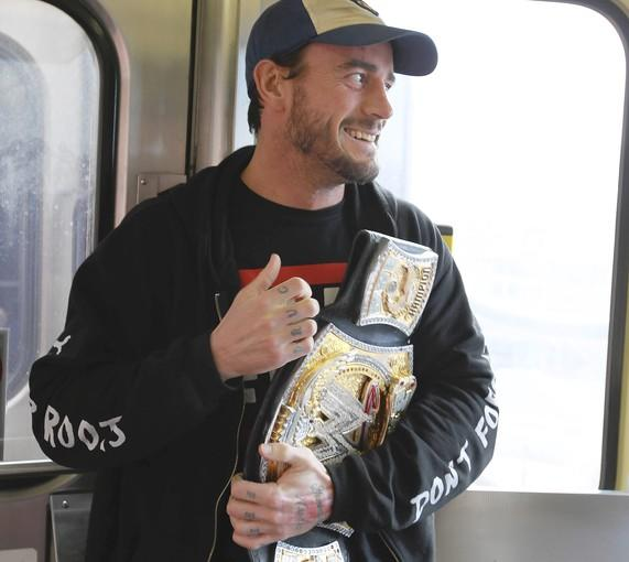 WWE World Champion CM Punk with his championship trophy on the CTA Blue Line on March 8. (Chicago Tribune/ Phil Velasquez)