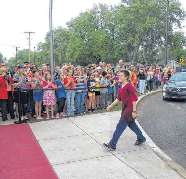 "Sixth-grader Thomas Few walks into Brandywine Elementary past waving fans at the premier of ""The Mystery of the Haunted Library Notes."" The movie was created by sixth-graders at the school."