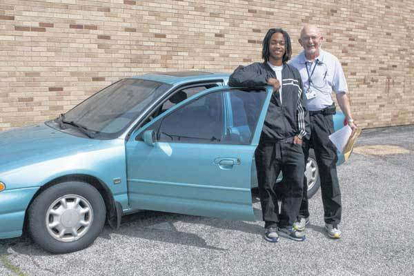 Dennis Scott, left, and Patrick Cottrell pose by Dennis' new car at Rise Up Academy in South Bend. Cottrell donated the car.