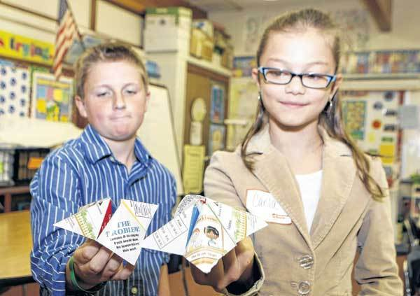 Warren Primary Center fourth-graders Matthew Hirschler, left, and Carla Castro hold up the business decision paper games used in a program at the school about earnings and saving money as part of schoolwide Junior Achievement Day with the help of 1st Source Bank volunteers.