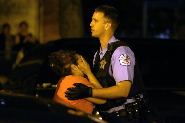 A woman who identified herself as the mother of a man who was killed is held back by police as she is overcome with emotion after arriving at the scene where people three were shot, including the one who died, in the 2500 of South Ridgeway Ave. in Chicago.