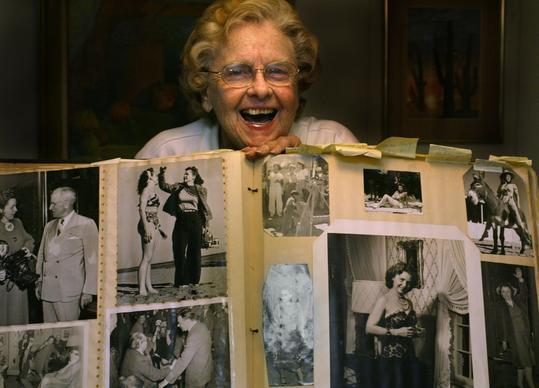 Helen Brush Jenkins, a pioneering news photographer in the early 1940s at the now defunct L.A. Daily News, holds up a scrapbook of her work for a Times profile in 20