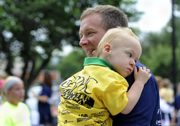 Matt Sprow of Baltimore carries his 2-year-old son, Lukas after finishing in the one mile fun run at the 25th annual GBMC Fathers Day 5K and one mile fun run, which benefits the GBMC Neonatal Intensive Care Unit. Lukas spent 5 months at the NICU.