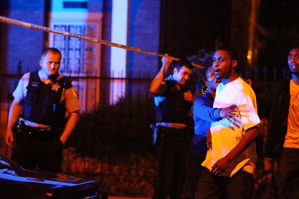 The brother of a man who was shot and killed by police has to be restrained at the scene of the incident on the 1600 block of South Springfield Avenue on Sunday. Police said the man was killed after he allegedly raised a 9-millimeter handgun in their direction after bailing from a moving car early Sunday morning.