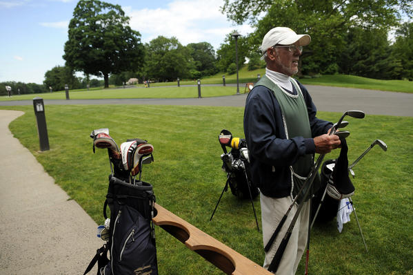 Kenny Gilmond cleans some clubs for a member he caddied for at New Haven Country Club Thursday afternoon. Carrying a bag for a member is just one of the the things a caddie does. Cleaning their clubs and giving helpful tips on the course are others, all of which has allowed Gilmond to make a career that has spanned six decades, beginning in 1963.