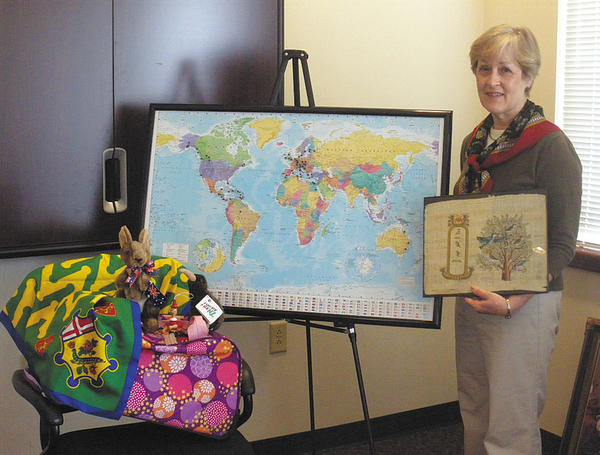 Club member Diane Braun is shown with some of her souvenirs and a map of her travels.