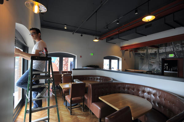 Restauranteur Mauro Daigle hangs blinds as the new Chesapeake restaurant prepares to open.