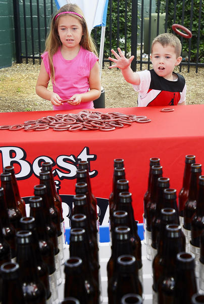Riley Burns, left, 7, and her brother, Jack Burns, right, 4, of Hagerstown, play the ring toss game under the Readers Digest Best of America tent Sunday afternoon at Municipal Stadium in Hagerstown.