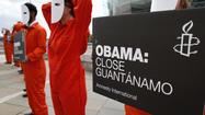 Amnesty International volunteers wear masks and orange suits depicting detainees at Guantanamo Bay