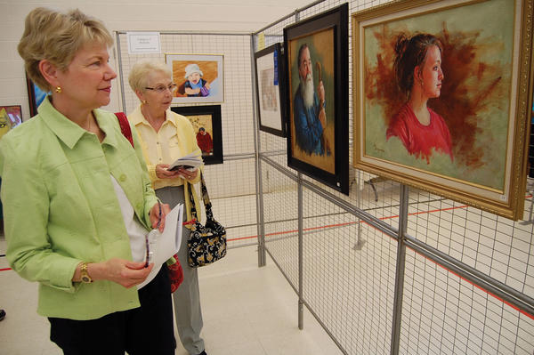 Friends Donna Gilbert, left, and Sara Taylor check out the pieces presented during the Franklin County (Pa.) Art Alliance's 42nd annual show. The show is open to the public through Thursday.