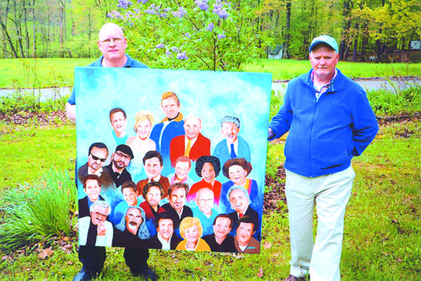 John Jagnow (left) and Jim Phillippi hold up a painting Phillippi made for the gospel singers, The Gaither group. Pictured in the painting are from left, front: J.D. Sumner, Guy Penrod, Bill Gaither, Gloria Gaither, Mark Lowry and Russ Taff. Second row: Kevin Williams, Wes Hampton, David Phelps, Michael English, Buddy Greene and Donnie Sumner. Third row: Gordon Mote, Ben Isaacs, Michael Booth, Anthony Burger, Lynda Randal and Vestal Goodman. Back: Ernie Haase, Joyce Martin, Danny Gaither, George Younce and Jake Hess.