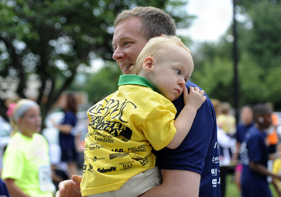 Matt Sprow of Baltimore carries his 2 year old son Lukas after finishing in the one mile fun run at the 25th annual GBMC Fathers Day 5K and one mile fun run, which benefits the GBMC Neonatal Intensive Care Unit. Lukas spent 5 months at the NICU after being born early.