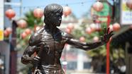 Officials in Chinatown unveiled a 7-foot bronze statue of Bruce Lee to a crowd of several hundred in the historical Central Plaza on Saturday night.