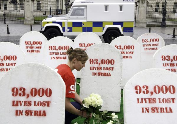 Oxfam protesters outside the Group of 8 summit in Lough, Northern Ireland, place flowers around mock gravestones symbolizing the 93,000 killed in Syria.