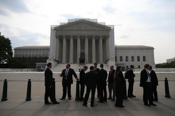 People stand in front of the Supreme Court in Washington.