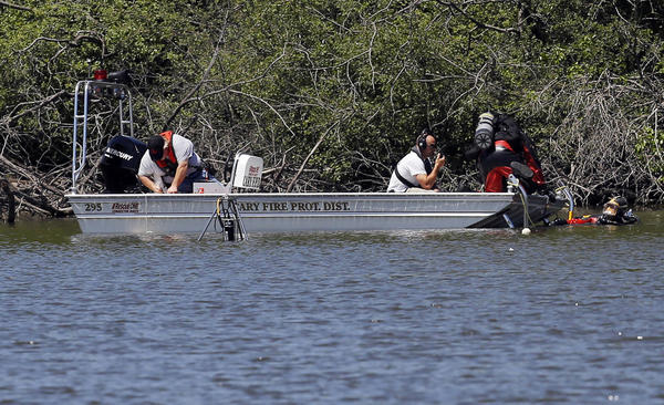 Divers search the waters across from the 200 block of Northwest Highway in Cary for evidence related to the 1999 missing person's case of Wendy Kimura.
