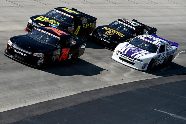 Mike Harmon, driver of the #74 Dave Novack Racing Chevrolet, leads Landon Cassill, driver of the #4 Flex Seal Chevrolet, Jeffrey Earnhardt, driver of the #79 Oath Keepers Ford, and Dexter Stacey, driver of the #92 Maddie's Place Ford, during the NASCAR Nationwide Series 5-hour ENERGY 200 at Dover International Speedway on June 1, 2013 in Dover, Del.