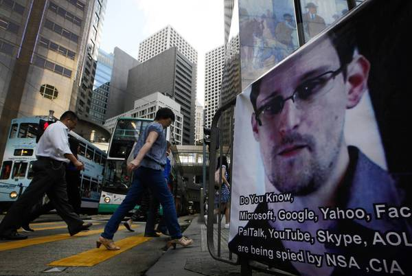 In Hong Kong, pedestrians pass a banner expressing support for Edward Snowden, the former U.S. government contractor who leaked information about surveillance programs. Snowden has been hiding in the Chinese territory.