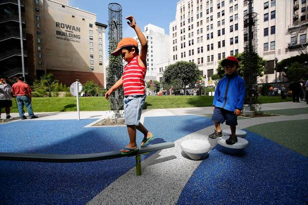 Matteo Walters, 4, left, keeps his balance while playing in the newly opened Spring Street Park in downtown Los Angele, while his brother Angelo, 3, observes. A parking lot used to occupy the site.