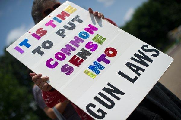 People calling for stricter gun laws hold signs during their weekly protest outside the White House. The Obama administration says it is doing what it can  to improve gun safety but that measures won't be effective without action by Congress.