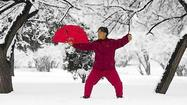 A woman practices tai chi with a fan after a snowfall in Shenyang