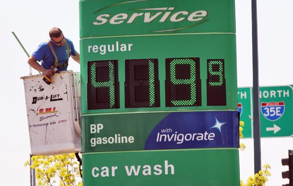 A technician works on a sign at a BP gas station in Vadnais Heights, Minn.