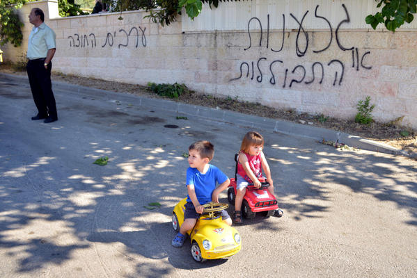 "Children play near a wall in the Arab Israeli village of Abu Gosh defaced with graffiti reading, ""Racism or assimilation"" and ""Arabs out."""