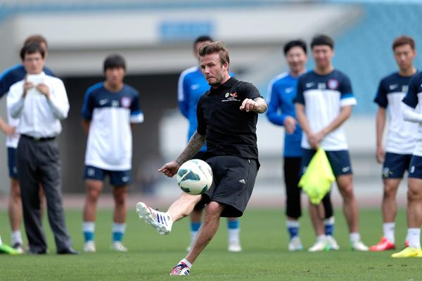 David Beckham, shown during a training session with Jiangsu Sainty players at Nanjing Olympic Sports Center in China on Tuesday, was reportedly invited to try out for the NFL.