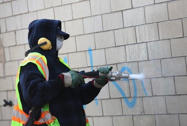A Chicago Streets and Sanitation worker removes graffiti with a mixture of water and baking soda.