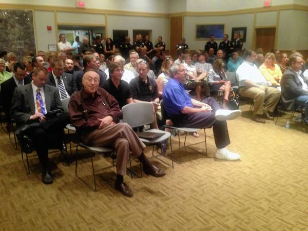 To a standing-room only crowd, Buffalo Grove village trustees Monday deterred a discussion and vote on a proposed assault weapons ban in the village until next month.
