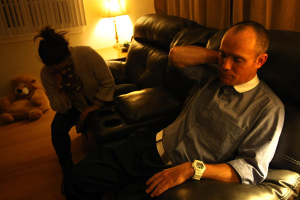 David Perdue rests next to his wife Lyzzette in their Redondo Beach home two days after Torrance police rammed his truck and shot at him during the Christopher Dorner manhunt.
