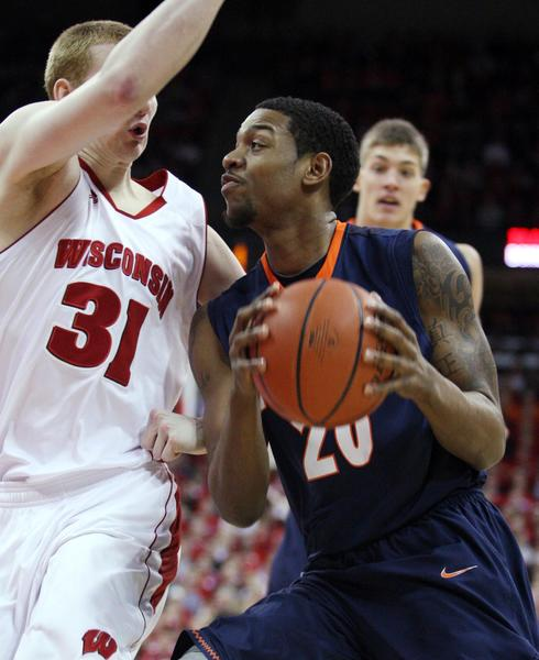 Myke Henry looks to shoot as Wisconsin Badgers forward Mike Bruesewitz defends last season.